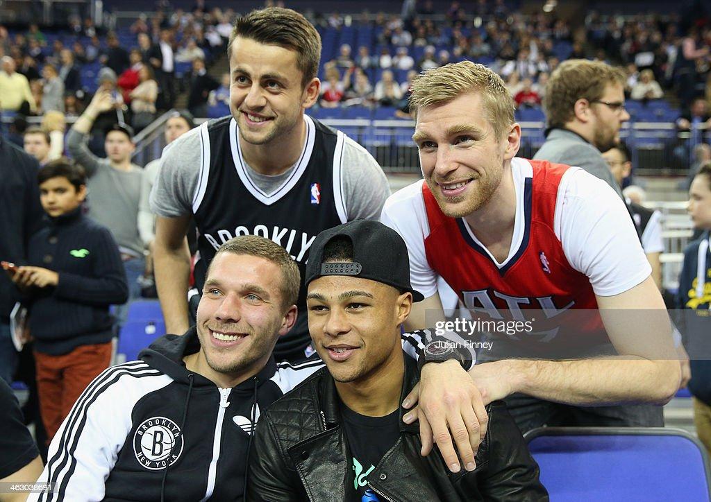 Arsenal players Lukas Podolski, Serge Gnabry, Per Mertesacker and Lukasz Fabianski before the Eastern Conference NBA match between Brooklyn Nets and Atlanta Hawks at O2 Arena on January 16, 2014 in London, England.