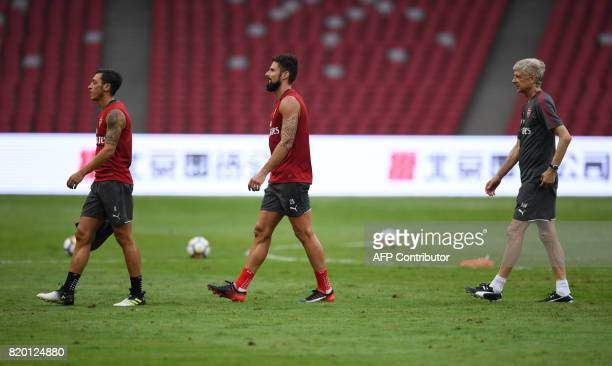 Arsenal players Mesut Ozil Olivier Giroud and coach Arsene Wenger take part in a football training session in Beijing's National Stadium known as the...