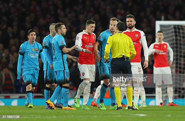 Arsenal players surround the referee Cuneyt Cakir during the UEFA Champions League round of 16 first leg match between Arsenal and Barcelona on...