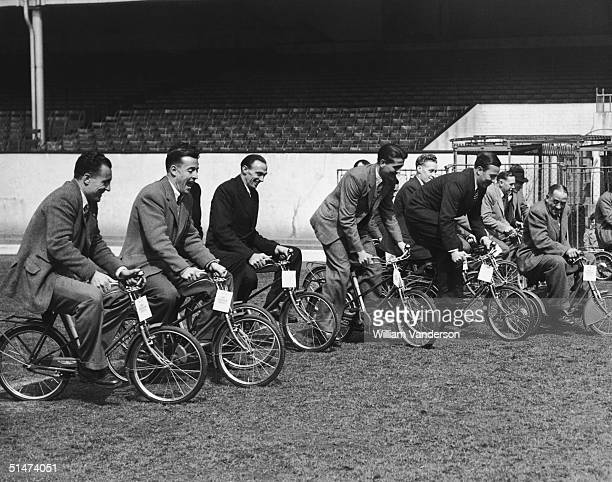 Arsenal players trying out a set of bikes donated by the British Cycle Company for their children during training at Highbury Stadium 28th April 1950...