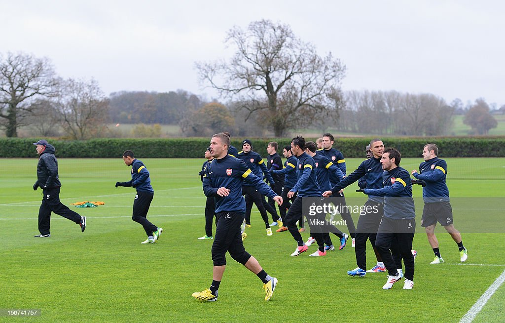Arsenal players, with Lukas Podolski in the foreground, warm up during a training session at London Colney ahead of tomorrow's UEFA Champions League Group B match against Montpellier on November 20, 2012 in St Albans, England.