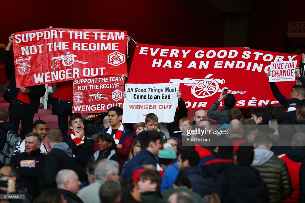 Arsenal supporters hold protest banners during the Barclays Premier League match between Arsenal and Norwich City at The Emirates Stadium on April 30, 2016 in London, England