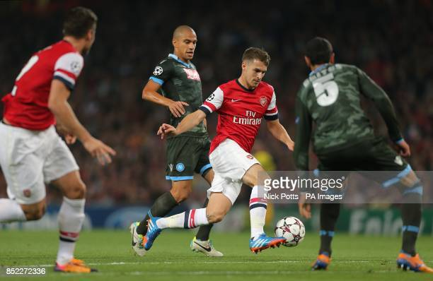 Arsenal's Aaron Ramsey attempts to run in between Napoli's Gokhan Inler and Miguel Britos