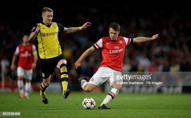 Arsenal's Aaron Ramsey gets a shot on goal past Borussia Dortmund's Marco Reus during the UEFA Champions League Group F match at the Emirates Stadium...