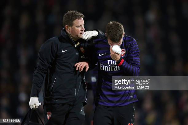Arsenal's Aaron Ramsey is led off with a facial injury by physio Colin Lewin