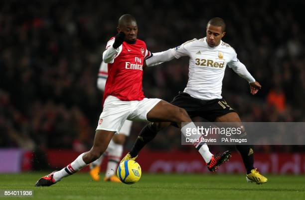 Arsenal's Abou Diaby is challenged by Swansea's Wayne Routledge during the FA Cup Third Round Replay at the Emirates Stadium London