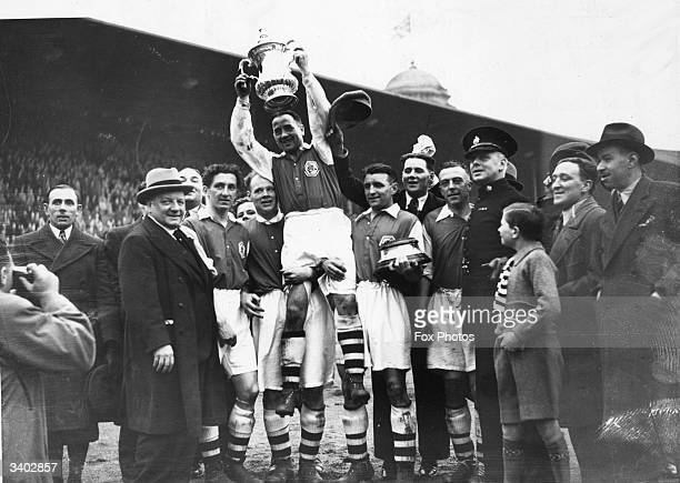 Arsenal's Alex James and the FA Cup trophy are lifted in victory after Arsenal's 10 victory over Sheffield United in the FA Cup final at Wembley...