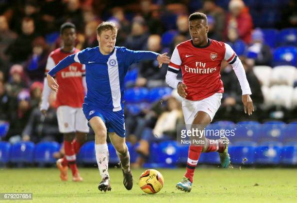 Arsenal's Alexander Iwobi holds off Peterborough United's Tom Conlon