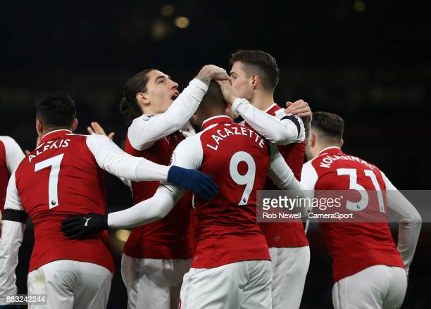 Arsenal's Alexandre Lacazette is congratulated by Hector Bellerin after scoring his side's first goal during the Premier League match between Arsenal...
