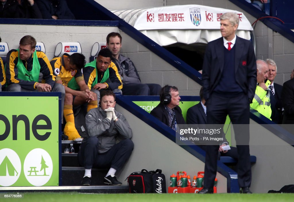 Arsenal's Alexis Sanchez on the bench (second from left) as manager Arsene Wenger stands on the touchline during the Premier League match at The Hawthorns, West Bromwich.
