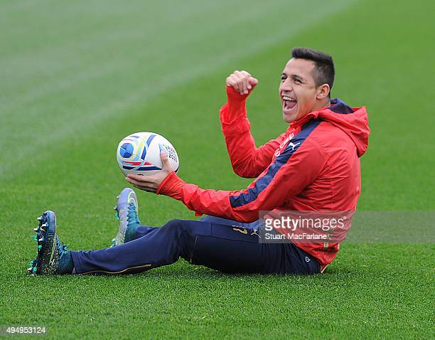 Arsenal's Alexis Sanchez warms up with a rugby ball before a training session at London Colney on October 30 2015 in St Albans England
