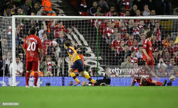 Arsenal's Andrey Arshavin celerbates after scoring the third goal Liverpool's Jamie Carragher sits dejected