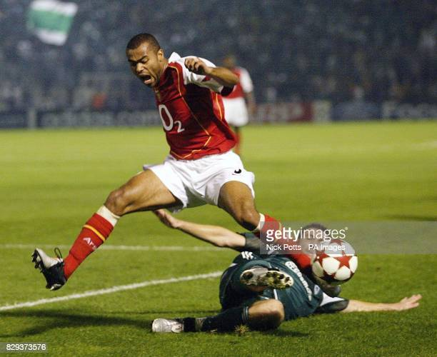 Arsenal's Ashley Cole skips over the tackle from Panathinaikos' Yannis Goumas during the UEFA Champions League Group E match at the Apostolos...