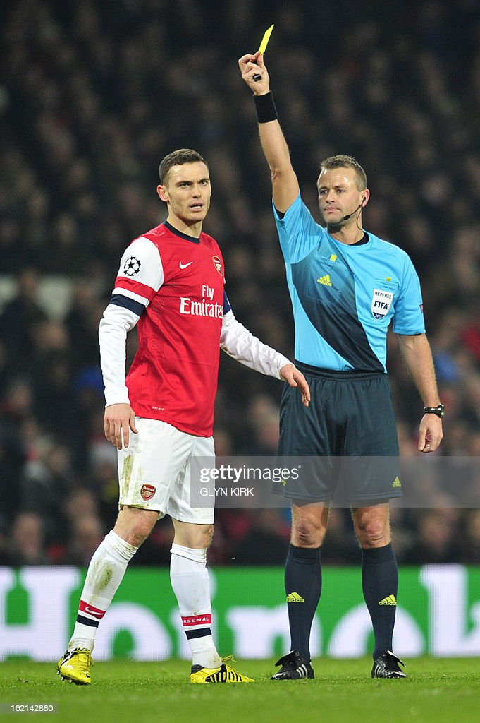 Arsenal's Belgian defender Thomas Vermaelen (L) is shown the yellow card by Norwegian referee Svein Oddvar Moen (R) during the UEFA Champions League round of 16 football match between Arsenal and Bayern Munich at the Emirates Stadium in north London on February 19, 2013.