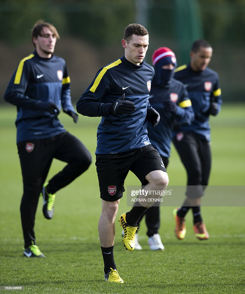 Arsenal's Belgian defender Thomas Vermaelen (C) warms up during a training session at the club's complex in London Colney on March 12, 2013 ahead of the team's last 16 UEFA Champions League football match against Bayern Munich in Germany on March 13.