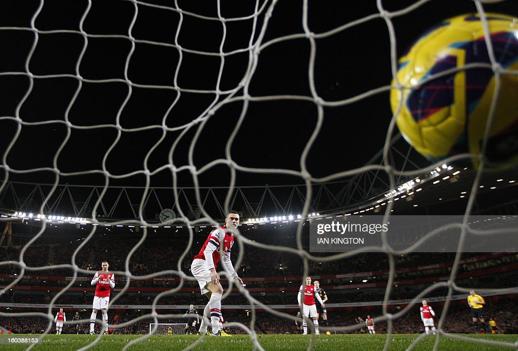 "Arsenal's Belgium defender Thomas Vermaelen (C) looks on as Liverpool's Uruguayan striker Luis Suarez (not pictured) scores during the English Premier League football match between Arsenal and Liverpool at The Emirates Stadium in north London on January 30, 2013. USE. No use with unauthorized audio, video, data, fixture lists, club/league logos or ""live"" services. Online in-match use limited to 45 images, no video emulation. No use in betting, games or single club/league/player publications."