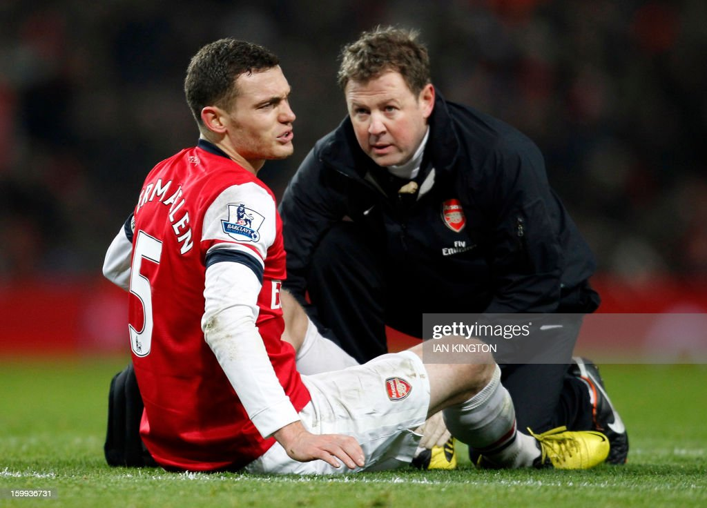Arsenal's Belgium defender Thomas Vermaelen receives treatment during the English Premier League football match between Arsenal and West Ham United at The Emirates Stadium in London on January 23, 2013. USE. No use with unauthorised audio, video, data, fixture lists, club/league logos or 'live' services. Online in-match use limited to 45 images, no video emulation. No use in betting, games or single club/league/player publications.