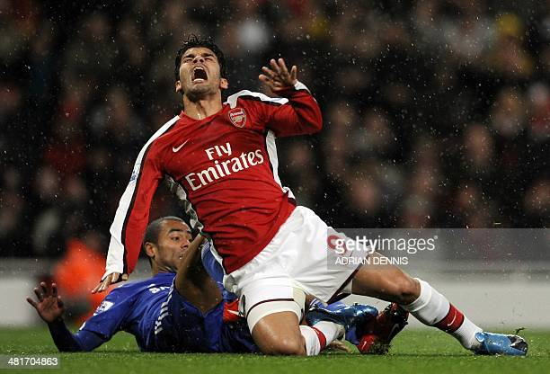 Arsenal's Brazilian forward Eduardo goes down under a challenge from Chelsea's Ashley Cole during the Premiership match at the Emirates Stadium in...