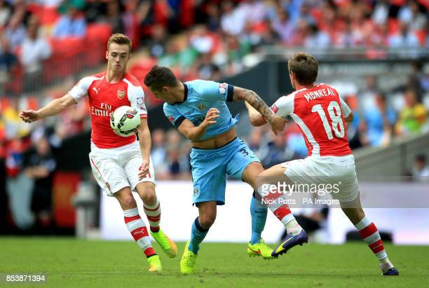 Arsenal's Calum Chambers and Nacho Monreal help each other to win the ball beating Manchester City's Stevan Jovetic