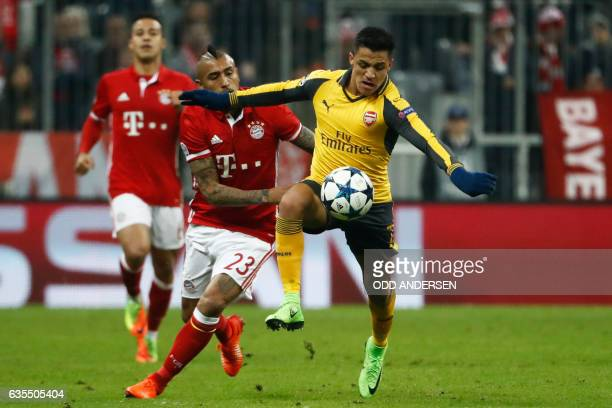 Arsenal's Chilean striker Alexis Sanchez and Bayern Munich's Chilean midfielder Arturo Vidal vie for the ball during the UEFA Champions League round...