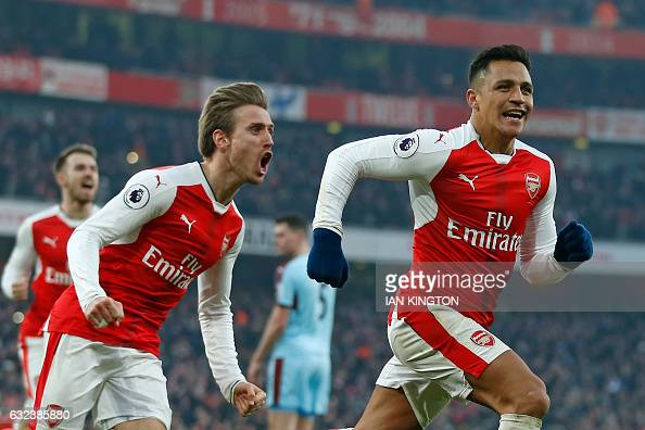 Arsenal's Chilean striker Alexis Sanchez celebrates with Arsenal's Spanish defender Nacho Monreal after scoring their late winner from the penalty...