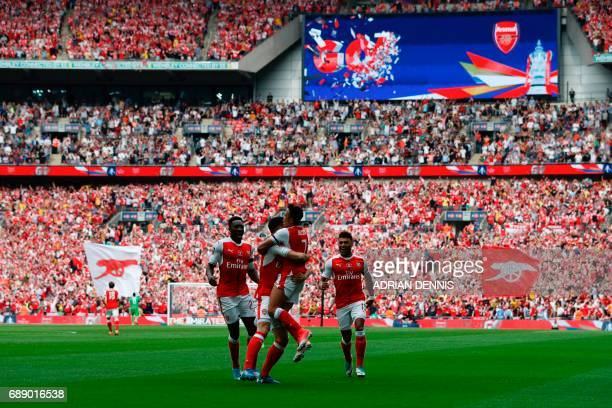Arsenal's Chilean striker Alexis Sanchez celebrates with teammates after scoring the opening goal of the English FA Cup final football match between...
