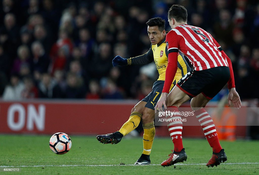 Arsenal's Chilean striker Alexis Sanchez (L) corsses the ball to Arsenal's English midfielder Theo Walcott (unseen), setting him up to score the team's fifth goal during the English FA Cup fourth round football match between Southampton and Arsenal at St Mary's in Southampton, southern England on January 28, 2017. / AFP / Adrian DENNIS / RESTRICTED TO EDITORIAL USE. No use with unauthorized audio, video, data, fixture lists, club/league logos or 'live' services. Online in-match use limited to 75 images, no video emulation. No use in betting, games or single club/league/player publications. /
