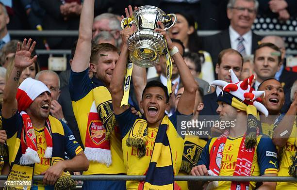 Arsenal's Chilean striker Alexis Sanchez holds up the trophy as Arsenal's Spanish midfielder Santi Cazorla and Arsenal's English midfielder Jack...
