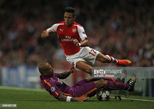Arsenal's Chilean striker Alexis Sanchez is tackled by Galatasaray's Brazilian midfielder Felipe Melo during the UEFA Champions League Group D...