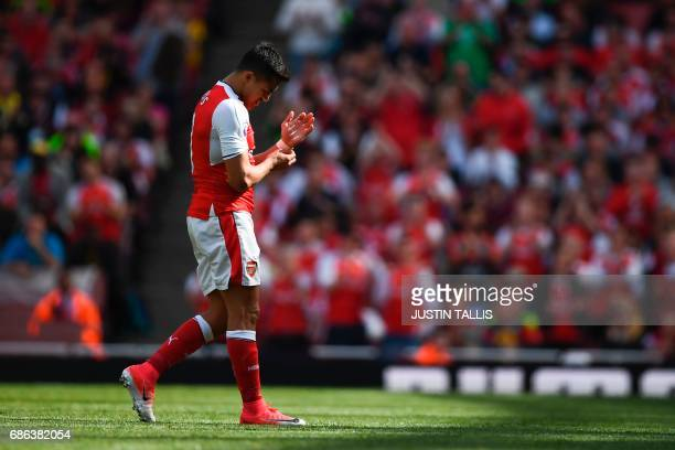 Arsenal's Chilean striker Alexis Sanchez leaves the pitch during the English Premier League football match between Arsenal and Everton at the...