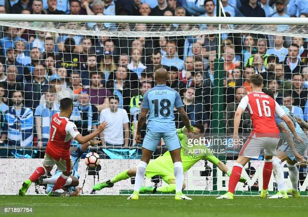 Arsenal's Chilean striker Alexis Sanchez scores the second goal during the FA Cup semifinal football match between Arsenal and Manchester City at...