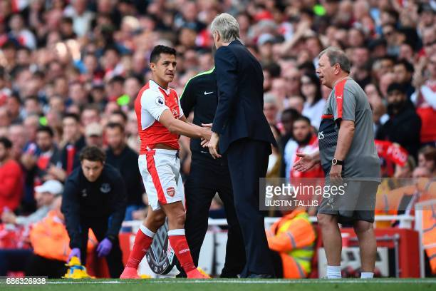 Arsenal's Chilean striker Alexis Sanchez shakes hands with Arsenal's French manager Arsene Wenger as he goes off substituted during the English...