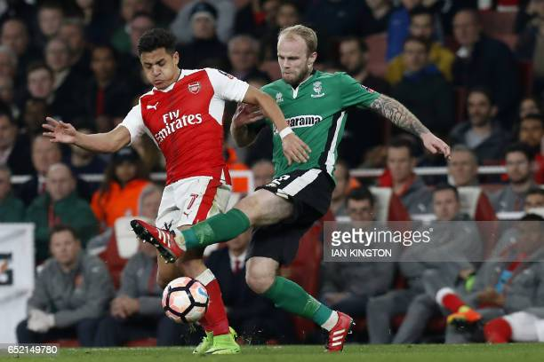 Arsenal's Chilean striker Alexis Sanchez vies with Lincoln City's English defender Bradley Wood during the English FA cup quarter final football...
