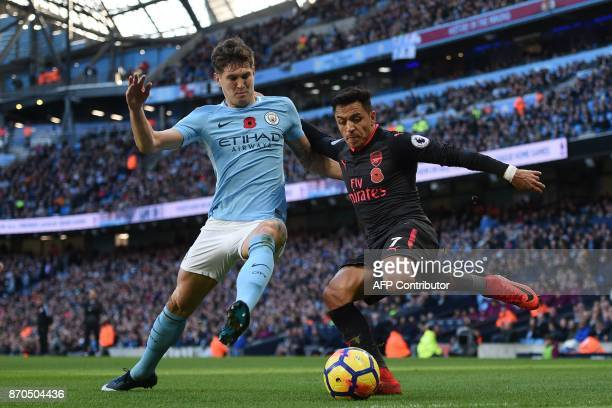 Arsenal's Chilean striker Alexis Sanchez vies with Manchester City's English defender John Stones during the English Premier League football match...