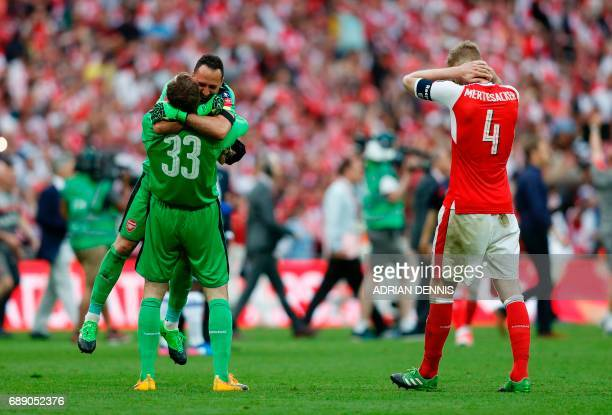 Arsenal's Colombian goalkeeper David Ospina and Arsenal's Czech goalkeeper Petr Cech celebrates as Arsenal's German defender Per Mertesacker reacts...