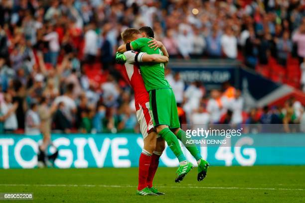 Arsenal's Colombian goalkeeper David Ospina and Arsenal's German defender Per Mertesacker celebrate their win on the final whistle of the English FA...