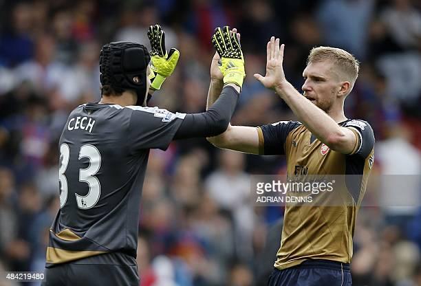 Arsenal's Czech goalkeeper Petr Cech and Arsenal's German defender Per Mertesacker celebrate their win after the English Premier League football...