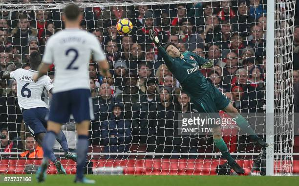 Arsenal's Czech goalkeeper Petr Cech dices to make a save from a shot by Tottenham Hotspur's English defender Eric Dier during the English Premier...