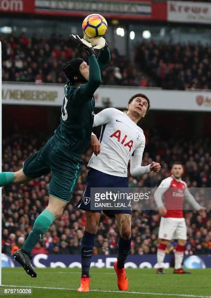 Arsenal's Czech goalkeeper Petr Cech dives to clear the ball from the path of Tottenham Hotspur's English midfielder Dele Alli during the English...