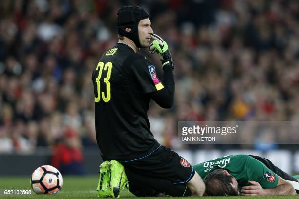 Arsenal's Czech goalkeeper Petr Cech gestures to the officials as Lincoln City's English striker Matt Rhead lies injured during the English FA cup...