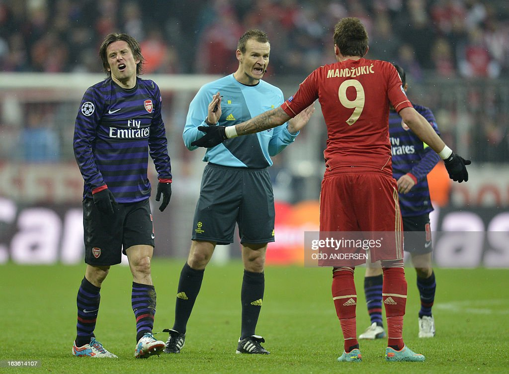Arsenal´s Czech midfielder Tomas Rosicky (L) and Bayern Munich's Croatian striker Mario Mandzukic (R) discuss with Czech referee Pavel Kralovec (C) during the UEFA Champions League Round of 16 second-leg football match FC Bayern Munich vs FC Arsenal London in Munich, southern Germany, on March 13, 2013.