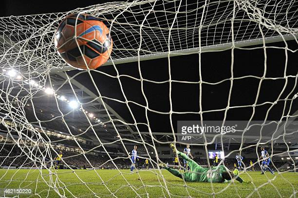 Arsenal's Czech midfielder Tomas Rosicky scores his team's third goal past Brighton's English goalkeeper David Stockdale during the FA Cup fourth...