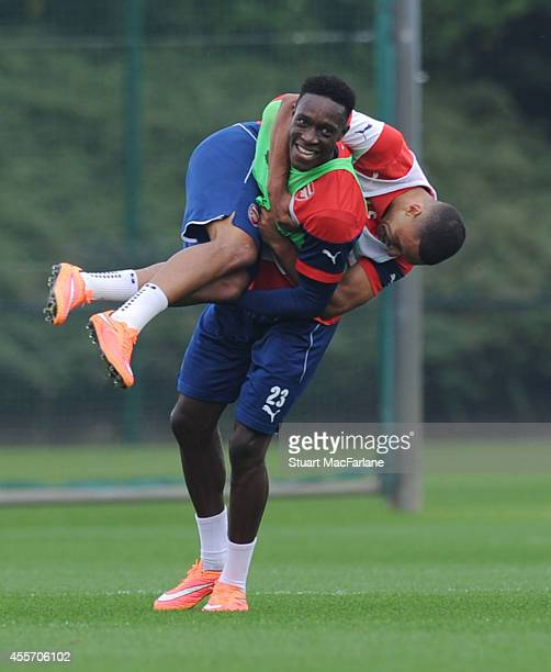 Arsenal's Danny Welbeck carries Alex OxladeChamberlain during a training session at London Colney on September 19 2014 in St Albans England