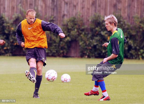 Arsenal's Denis Bergkamp fires a shot past teammate Alexsander Hleb during a training session at London Colney