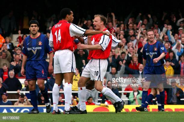 Arsenal's Dennis Bergkamp celebrates his goal with Thierry Henry as the Sunderland players Claudio Reyna and Jody Craddock look stunned