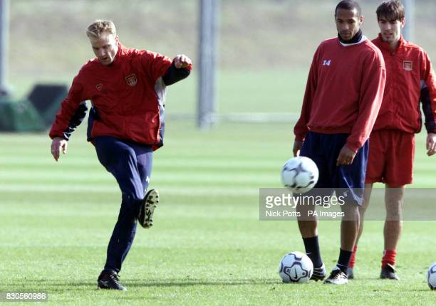 LEAGUE Arsenal's Dennis Bergkamp practises his free kicks while Thierry Henry and Robert Pires watch during a light training session at London Colney...