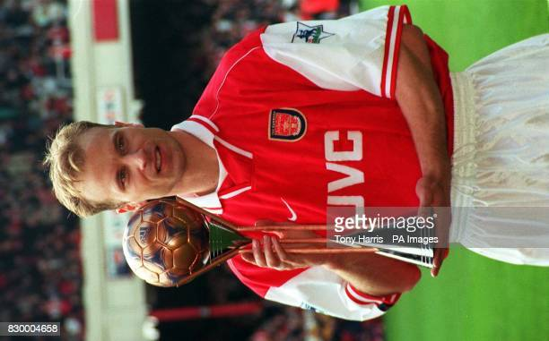 Arsenal's Dennis Bergkamp receives the third place World Player of the Year trophy on the pitch at Highbury ahead of their FA Carling Premiership...