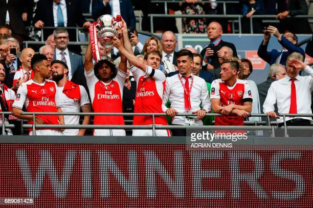 Arsenal's Egyptian midfielder Mohamed Elneny and Arsenal's Spanish defender Nacho Monreal lift the FA Cup trophy as Arsenal players celebrate their...