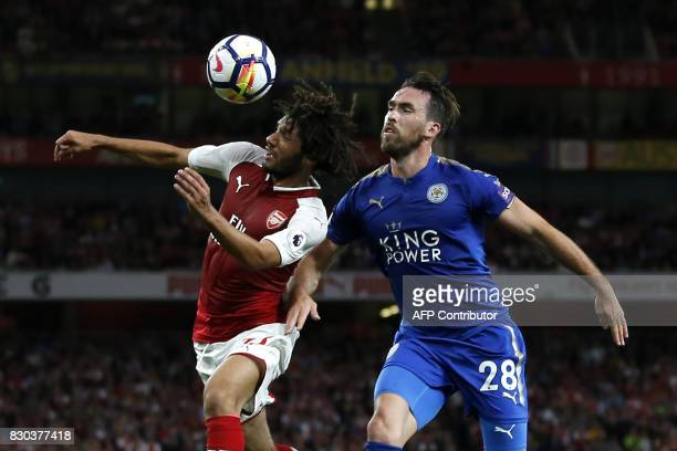 Arsenal's Egyptian midfielder Mohamed Elneny vies with Leicester City's Austrian defender Christian Fuchs during the English Premier League football...