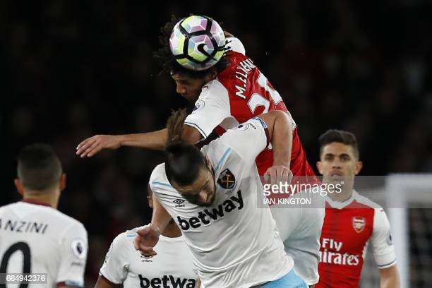 Arsenal's Egyptian midfielder Mohamed Elneny wins a header from West Ham United's English striker Andy Carroll during the English Premier League...